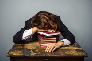 businesswoman sleeping on stack of books
