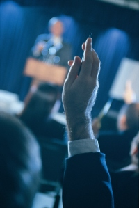 Man in audience raising hand